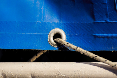 old rusty eyelets on an aged blue coated plastic canvas
