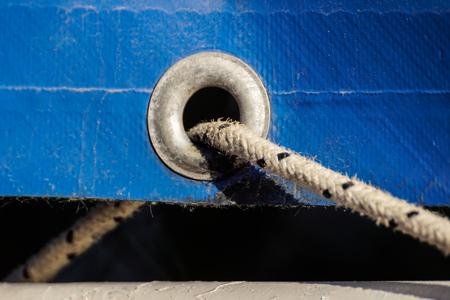 Vieux oeillets rouillés sur une vieille toile de plastique enduite bleu Banque d'images - 88229708