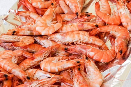 Shrimp cocktail background with a close up view of a group of fresh delicious refrigerated crustaceans as gourmet seafood for a party or dinner at a restaurant serving food from the sea Stock Photo