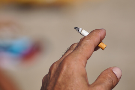 Smoking with cigarette butts ashtray on the sand on the beach and travel activity
