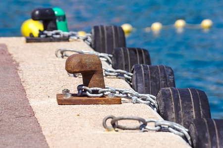 Old metal dock mooring pole with ring and rope for securing fishing boats