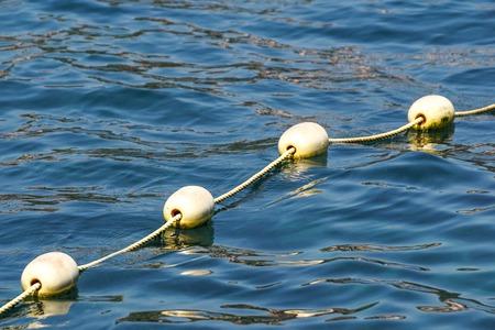 Lijn van gele boeien tegen de blauwe zee. Beperking op open water. Glans en rimpelingen op het water