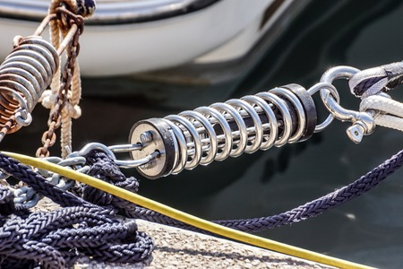 Metal cleat for mooring boats, bolted to the ground, with rope and shock absorber spring .