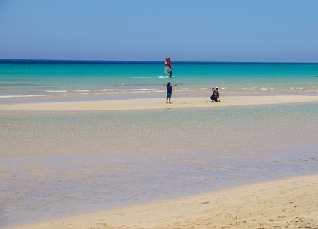 Fuerteventura , Spain 13 june 2017 : a couple takes pictures in the middle of the sea in a dry in the crystalline sea of the Canary Islands