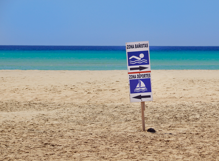 sign of bathing area on the beach for the safety of bathers compared to boats .  area sports and area bathers  write in Spanish language