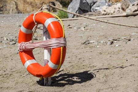 Life preserver on sandy beach somewhere near at sea
