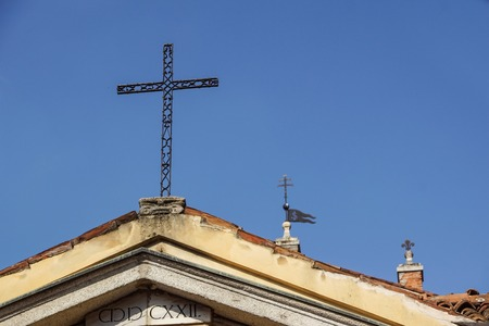 metal cross on a church roof with blue sky as a background