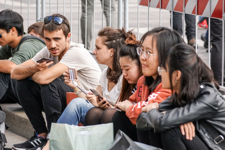 Milan ,Italy 04 March 2018 : young people sitting in the city square communicate using their smartphone. Editorial