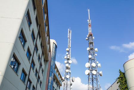 Mobile phone communication antenna tower with satellite dish on blue sky background, Telecommunication tower.