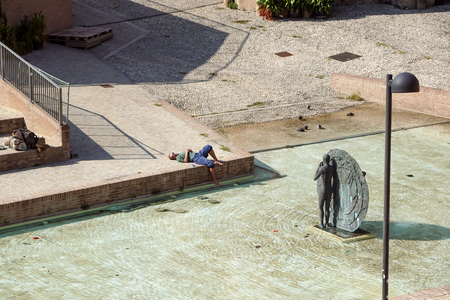 Bologna , Italy - 15 April 2018 : . an unidentified man relaxes by taking the sun in the modern city square .Afternoon relax at the downtown Editorial