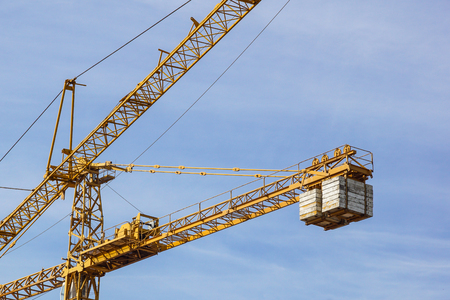 The elevating crane against the dark blue sky.