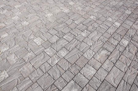Stone pavement in perspective. Stone pavement texture. Granite cobblestoned pavement background. Abstract background of a cobblestone pavement close-up, house