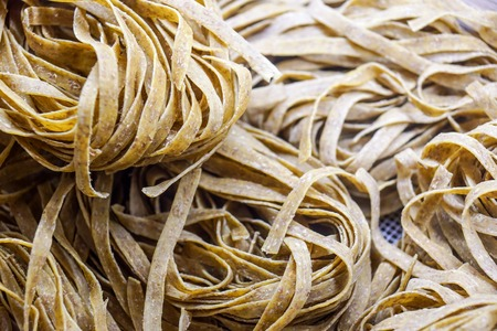 Fresh Pasta, close-up texture of Home made tagliatelle pasta flour ribbon noodle