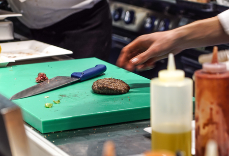 Preparing delicious burgers. Chef cooking meat burgers with bacon, cheese and vegetables, selective focus.