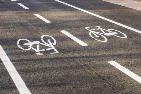 Separate bicycle lane for riding bicycles. White painted bike on asphalt. Ride ecological green urban transport Stock Photo