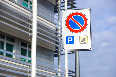 handicapped sign mark parking spot, disabled parking permit sign on pole with convenience store in gas station area background, copy space