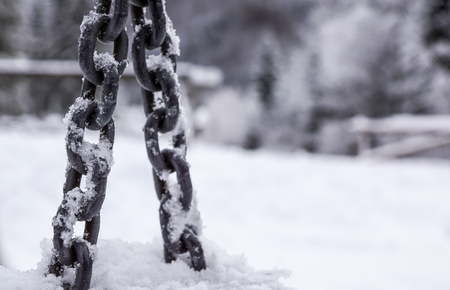 Anchor chain detail in hoarfrost in winter sunny day with selective focus
