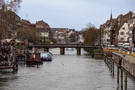 STRASBOURG, FRANCE - DECEMBER 11, 2011: people on waterfront of Ill river canal in old Strasbourg town.