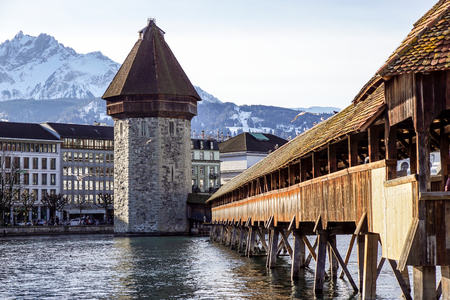LUCERNE, SWITZERLAND - december 2, 2017: Chapel Bridge and Water Tower, Lucerne. The wooden covered bridge spans the Reuss River with the with Mt. Pilauts rising in the background. Editorial