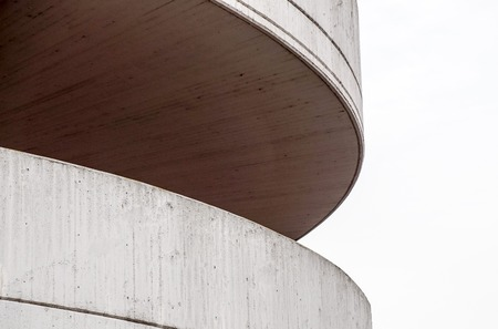 Detail at circular ramp to a parking garage. It is tan and made of cement blocks on the outside, cement slabs on the inside. It is a multi-level structure.