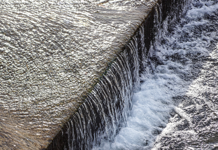 Regulated water flow of and irrigation channel that flows through the middle of a city. Фото со стока