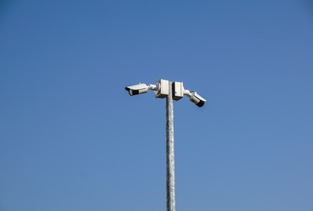 CCTV surveillance security camera on a black pole with blue sky background Stock Photo