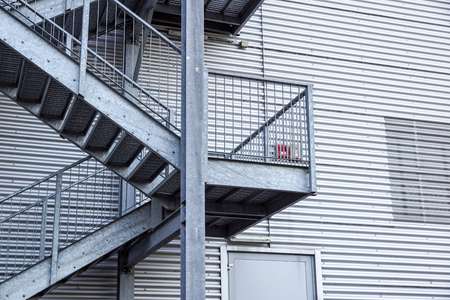Abstract industrial architecture fragment on blue sky background, metal stairway sections