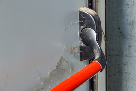 Closed up latch and door handle of emergency exit. Push bar and rail for panic exit. Stock Photo