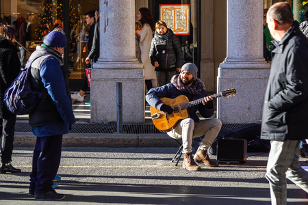 TURIN , ITALY 07 JANUARY 2017: Busker street artist playing guitar Editorial