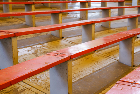 Rows of empty wooden stadium seats . close up