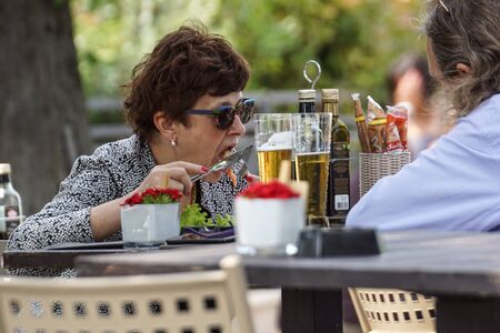 MILAN , ITALY 18 JUNE 2018 : A woman eats a food during a day at the restaurant Publikacyjne