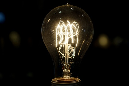 old light bulb glowing in dark . Close up