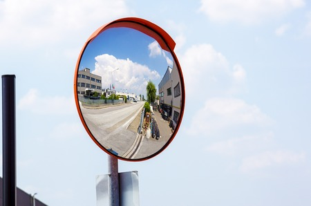 Outdoor convex safety mirror hanging on wall with reflection of an urban roadside view of cars parked along the street by residential apartment buildings.