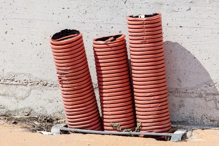 Red orange corrugated sheath for electric cables, on a building construction site