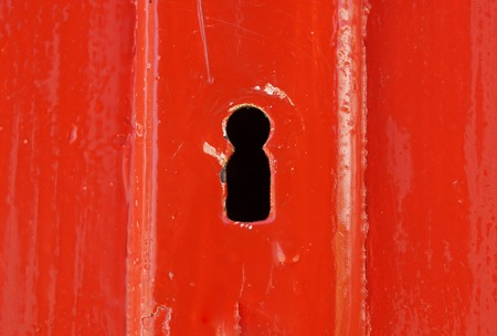 Detail of old wooden red painted door with heart shaped key hole
