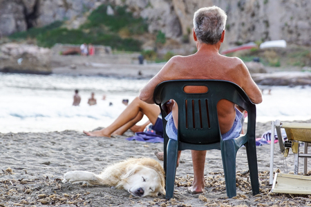 Mature man resting on a deck chair listening to music petting his dog on the beach Banco de Imagens