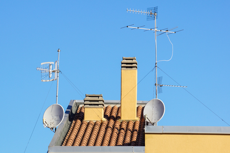 Satellite antenna and old roof antenna on a red roof Banco de Imagens - 122114033