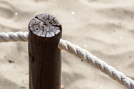 The walkway poles are tied with ropes and there is a rusty screw fastened.