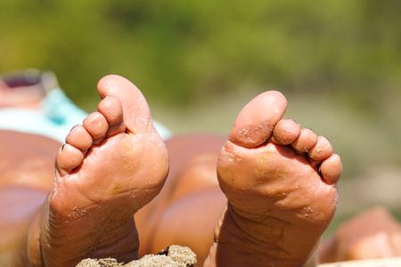 Vacation holidays. Woman feet closeup of girl relaxing on beach on sunbed enjoying sun on sunny summer day