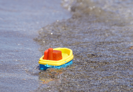 toy ship on the beach on a warm sunny summer day. Holidays at sea. Funny kids Banco de Imagens