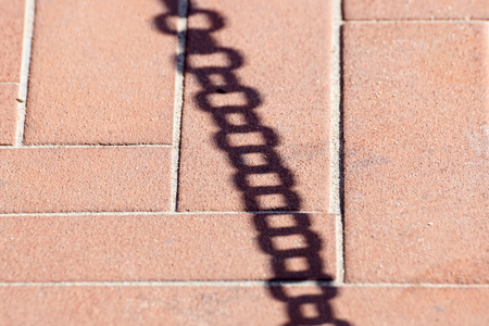 shadow on the floor of a metal chain