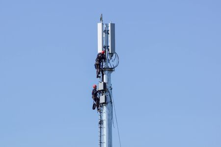 man working on high tower or pole of telecommunication. Maintenance on tower. Banco de Imagens