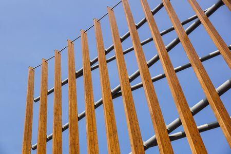 Modern architectural construction of wooden slats with half-round, openwork design . Banco de Imagens