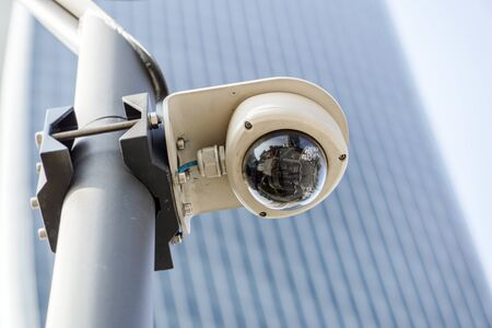Camera system guarding blue skyscraper office building with sky above Banco de Imagens - 125478951