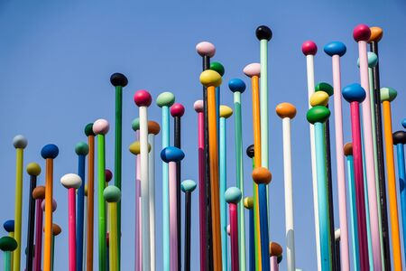Low angle of colorful thin poles against blue sky. Positive and bright background concept . Banco de Imagens - 125478473