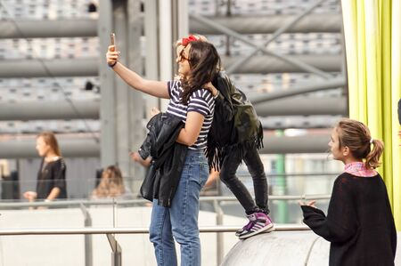 MILAN, ITALY 4 MAY 2019 : mother and daughter taking selfie photo together at square Editorial