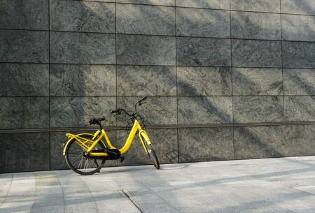 The retro bicycle parking against yellow wall Stock Photo