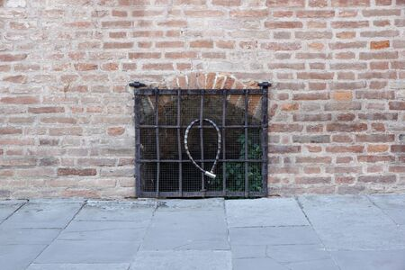 Window closed with a metal grate, in the facade of an old neglected house