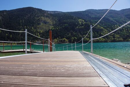 A wooden dock, pier, on a lake in summer sunny day Banco de Imagens