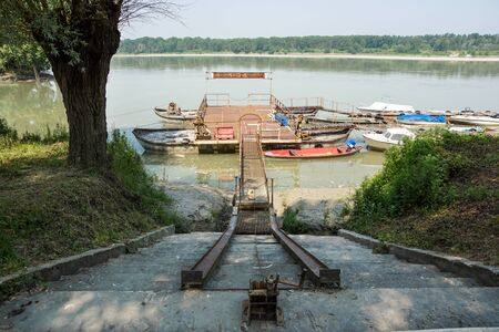 Traditional fishing boats tied up on the floating dock in picturesque surrounding of the big river .